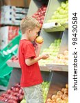 Little boy choosing bio apple food in fruit vegetable shopping store - stock photo