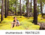 Woman hiker sitting relaxing after hiking eating apple in spring flowers in forest floor. Forest landscape, From Tenerife, Canary Islands, Spain - stock photo