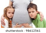 Grumpy kids not happy about their new sibling - listening to pregnant woman belly - stock photo