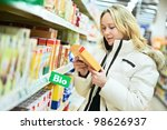woman choosing bio produces during food shopping in grocery store supermarket - stock photo
