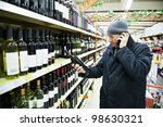 man choosing produces in vegetableduring weekly shopping at supermarket store - stock photo