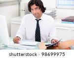 handsome man doing his paperwork | Shutterstock . vector #98699975