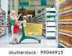 woman and children with shopping cart in supermarket store warwehouse - stock photo