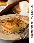Homemade focaccia with onion and rosemary on a ceramic plate. - stock photo