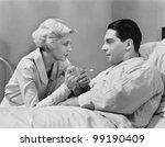 Woman feeding patient - stock photo