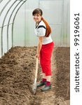 Happy female gardener spading with spade in hothouse - stock photo