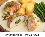 Chicken breasts stuffed with green beans and cheese wrapped in Parma ham. - stock photo