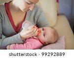 mother feeding infant girl with ... | Shutterstock . vector #99292889