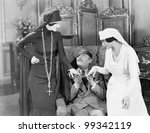 Young man with an eye patch being consoled by a nurse and a religious woman - stock photo