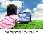 Girl playing with laptop. Shot outdoor at summer time - stock photo