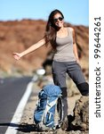 Travel hitchhiker woman happy standing on road side during holiday travel. Beautiful outdoors sporty woman model. - stock photo