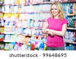 Happy smiling woman in front of household chemistry produces in shopping supermarket - stock photo