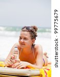 girl lies on a beach plank bed and holds a bottle with mineral water
