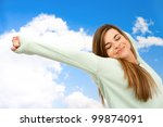 Young woman stretching arms outdoors on blue sky. - stock photo