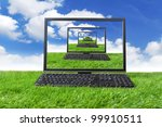 Computer on the green grass. Shot on meadow - stock photo