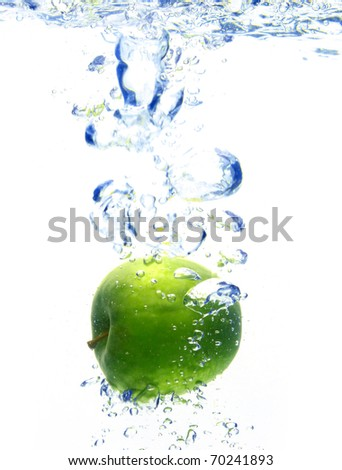 A background of bubbles forming in blue water after apple are dropped - stock photo