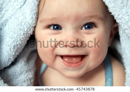 A beautiful smiling baby wrapped in a furry blue blanket - stock photo
