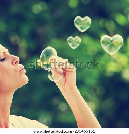 a beautiful woman blowing bubbles (one in the shape of a heart)  - stock photo