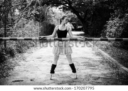 A beautiful young blond ballerina is standing on her toes in front of a boom gate like a security guard.This black and white photo has some beautiful classical lines.