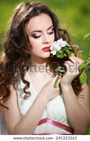 A beautiful young woman at the spring park - stock photo