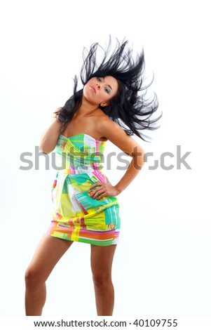 A beautiful young woman with her hair blowing and smiling, in front of a white background