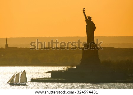 A boat sailing in front of the Statue of Liberty at sunset in New York City, USA. - stock photo