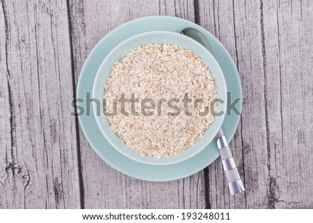 A Bowl of Oats on a Rustic Table - stock photo