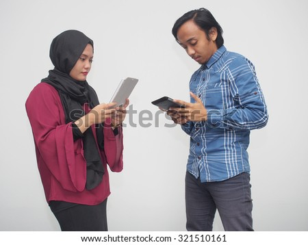A boy and a girl playing with mobile gadgets. - stock photo