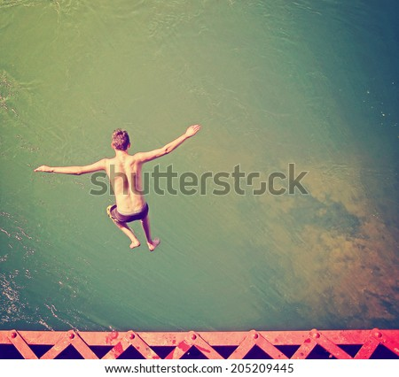 a boy jumping of an old train trestle bridge into a river done  - stock photo