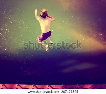 a boy jumping of an old train trestle bridge into a river done with a retro vintage instagram filter  - stock photo