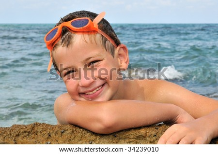 A boy with a  goggles for diving, poses a photographer