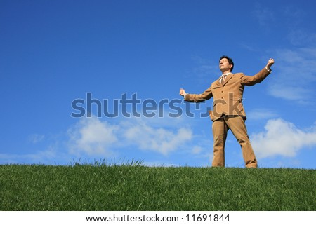 A business man standing with fists clenched in victory - stock photo