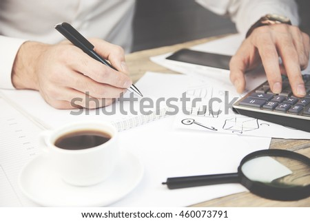 A Businessman Calculating Bills Using Calculator