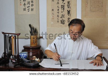 A calligrapher writing chinese calligraphy - stock photo