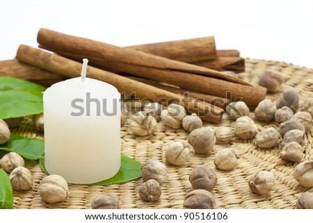 A candle with herb on a bamboo mat - stock photo