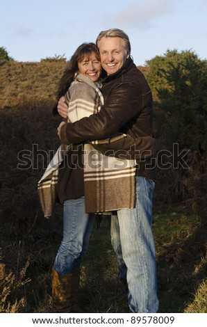 A color portrait photo of a good looking couple in their forties cuddling up to each other and smiling towards the camera during a day out in the countryside. - stock photo