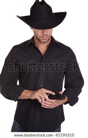 A cowboy in his black hat looking down at the gun in his hand. - stock photo