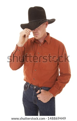 A cowboy is standing with one hand on his hat.
