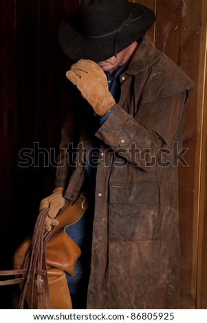 A cowboy standing up against a wall holding on to his hat with his head down. - stock photo