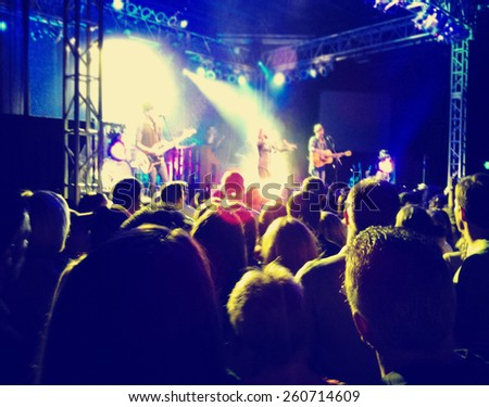 a crowd of people at a concert toned with a retro vintage instagram filter effect  - stock photo