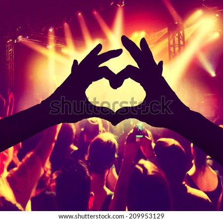a crowd of people at a concert with a heart silhouette toned with a retro vintage instagram filter  - stock photo