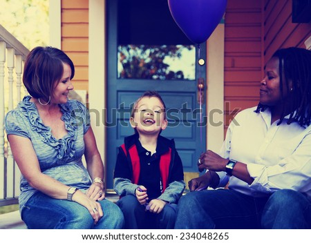 a cute family sitting on a porch toned with a retro vintage instagram filter  - stock photo