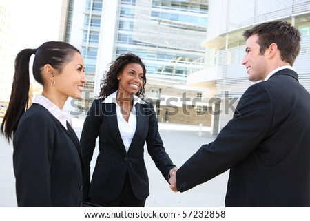 A diverse attractive man and woman business team at office building handshake - stock photo