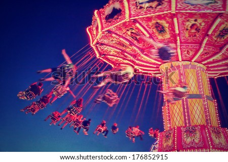 a fair ride shot with a long exposure at night done with a retro vintage instagram filter  - stock photo
