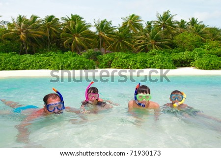 A family snorkeling in the water together.