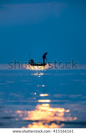 A fisherman's boat on the lake in the early morning - stock photo
