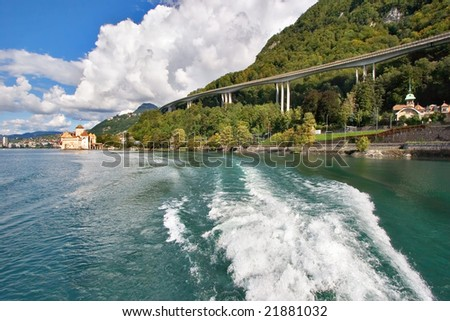 A foamy trace of a walking boat along coast of lake Leman in Switzerland and a motorway on coast - stock photo