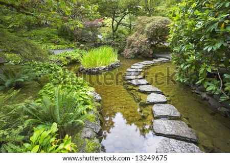 A footpath from stones laid with brick through a fine pond in Japanese garden, during a rain - stock photo