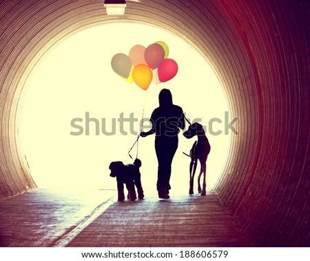 a girl at the end of a tunnel holding balloons and two dogs done with an instagram vintage retro filter  - stock photo