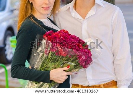 A girl holding a bouquet of flowers in their hands